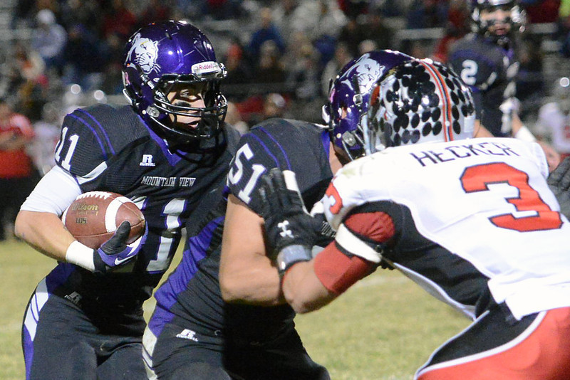 Mountain View High School's Jeremiah Clymer (11) runs behind teammate Daniel Carreon (51) as he blocks Loveland defender Greg Hecker in the first quarter of their game on Friday, Nov. 2, 2012 at Patterson Stadium.