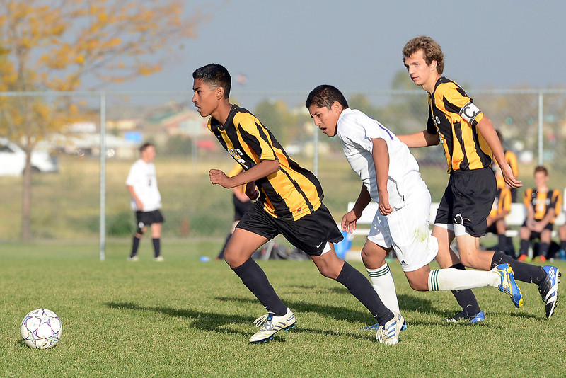 Thompson Valley High School's Fernando Rivera, left, dribbles ahead of teammate Nash Doughman, right, and Mountain View's Jonathan Hernandez in the second half of their match on Wednesday, Oct. 3, 2012 at MVHS.