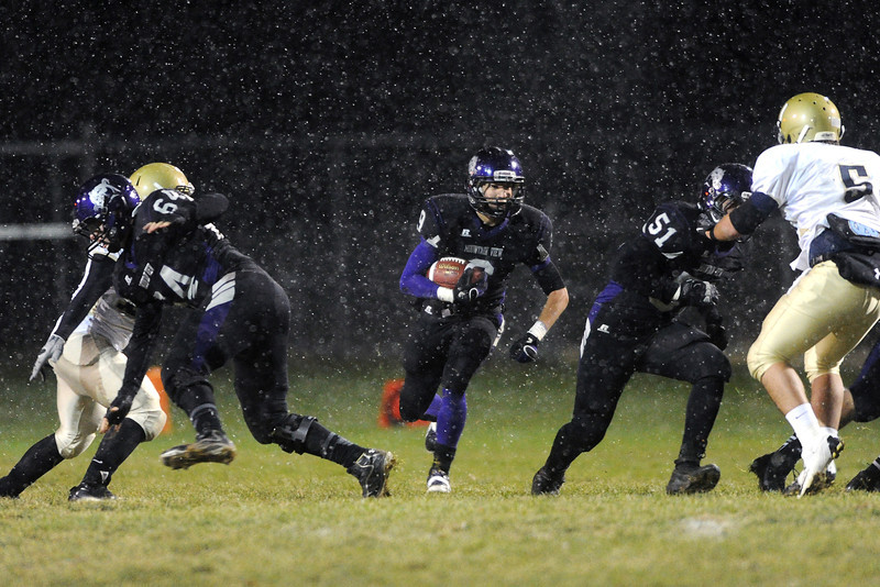 Mountain View High School running back Connor Logan, middle, cuts through a hole in the line behind teammates Justin Clinton (64) and Danniel Carreon (51) in the first quarter of their game against Greeley West on Thursday, Oct. 25, 2012 at Patterson Stadium