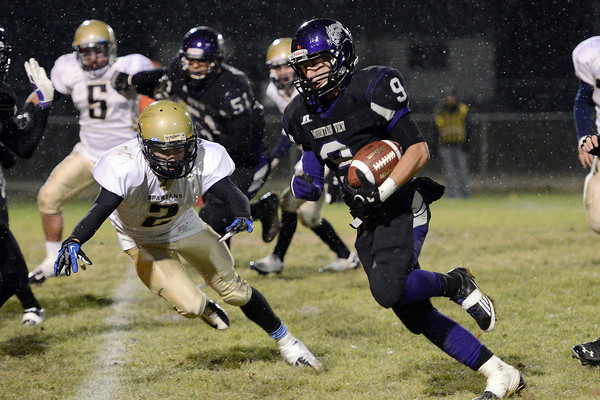 Mountain View High School's Connor Logan (9) runs around Greeley West defender Matthew Brunning (2) in the second quarter of their game Thursday, Oct. 25, 2012 at Patterson Stadium.