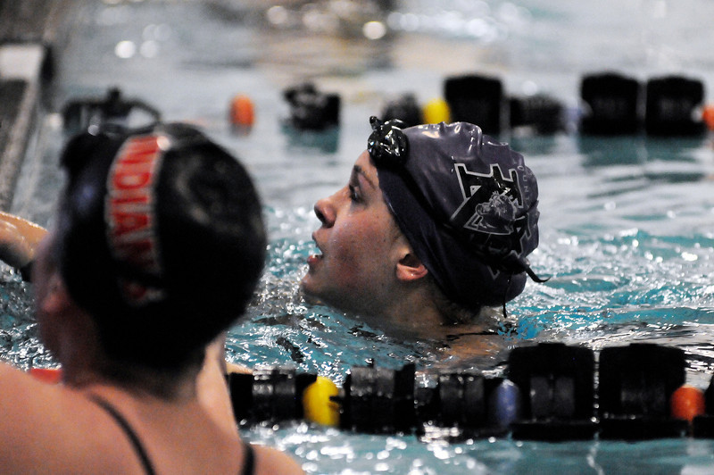 Jess Reed-Baum looks to the scoreboard after swimming the 100-yard butterfly event during Thursday evening's Loveland City Meet at Mountain View High School.