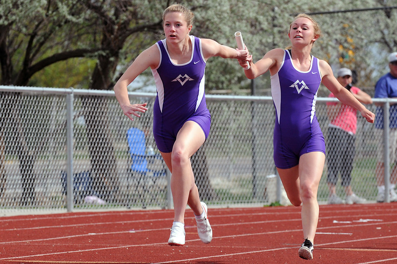 Mountain View High School senior Jacey Gordley, right, passes the baton to teammate junior Ashlee Wenrick while competing in the 400-meter relay Tuesday during the Northern Conference Track and Field Championships at Broomfield High School.