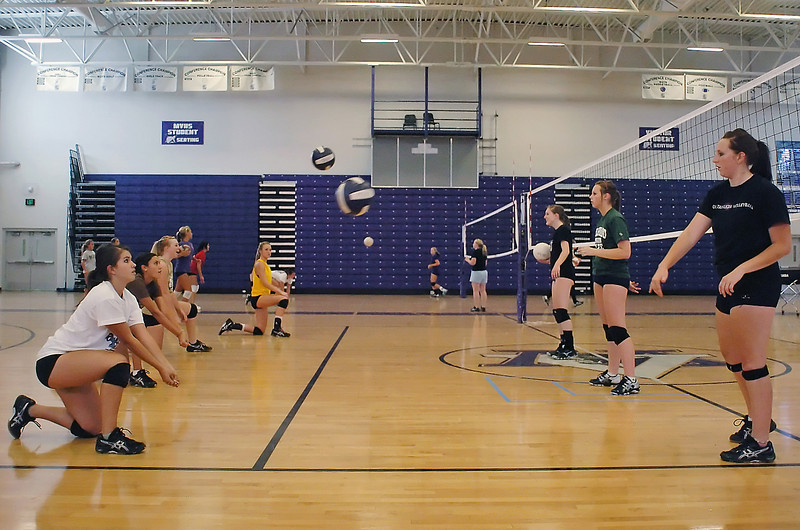 Mountain View High School junior Tamika Bjork, left, and senior Ashley Olson, right, and their volleyball teammates work on a drill during practice Friday at the school.