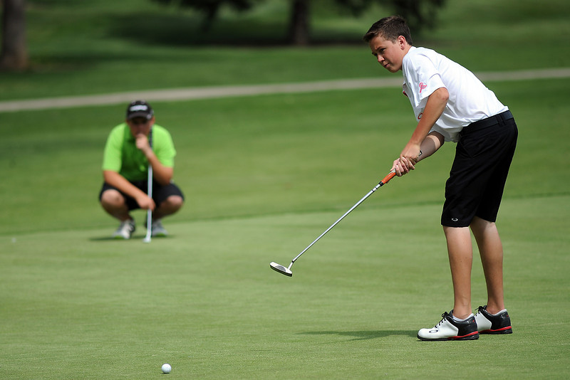 Alec Steine, 17, hits a putt on No. 8 while Evan Buchalski looks on during the Junior Optimist Golf Tournament on Monday, June 3, 2013 at The Olde Course at Loveland.