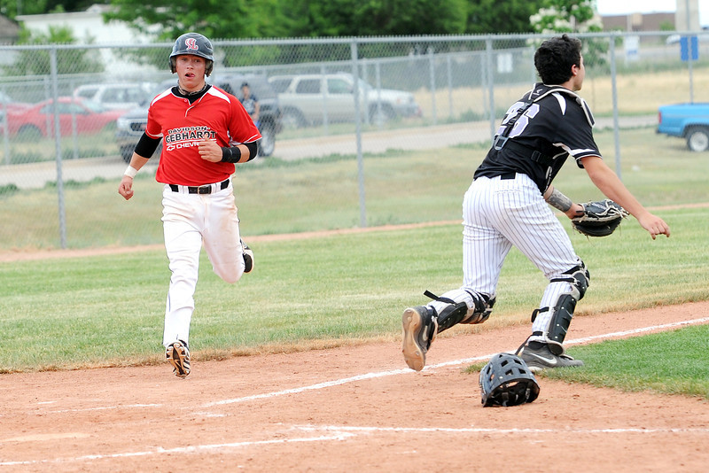 Davidson Chevrolet's [number 5] scores a run behind Johnson's Corner catcher Dakotah Shea-Shelley during their game on Friday, June 21, 2013 at Brock Field.