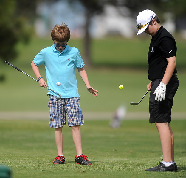 From left, Elliot Gitt, 10, and Chase Corlett, 13, dribble golf balls at the No. 8 tee box of The Olde Course golf course, Monday afternoon, in Loveland, Colo.