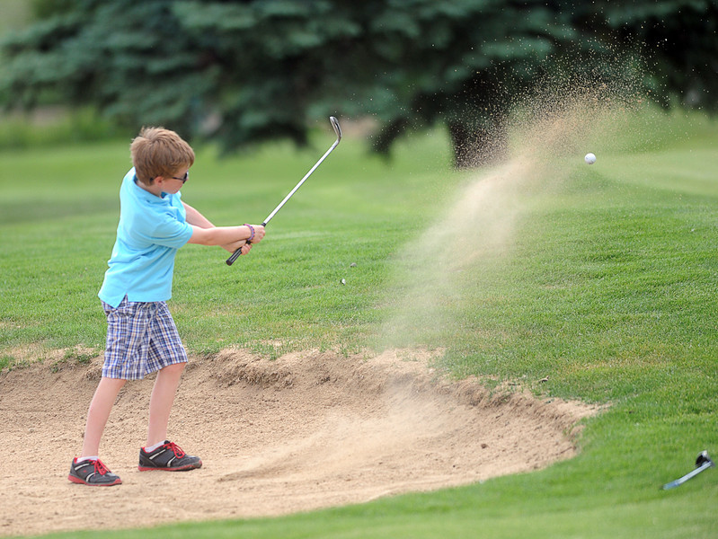 Elliott Gitt, 10, chips his way out of a sand trap at hole seven of The Olde Course golf course , Monday afternoon, In Loveland, Colo.