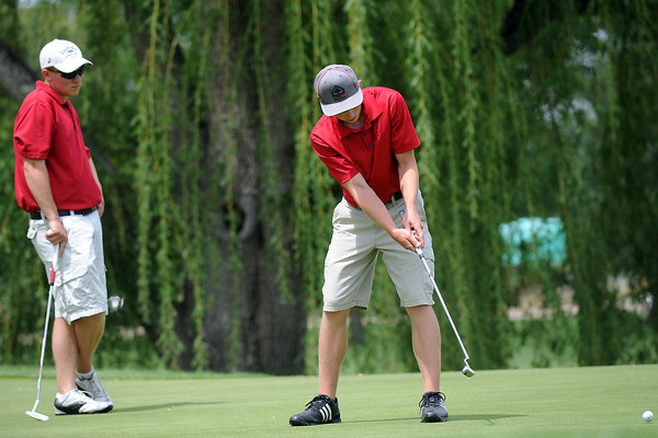 Alex Liss, 17, front, hits a putt on No. 5 as Hayden Trimble, 17, looks on while competing in the Junior Optimist Golf Tournament on Monday, June 3, 2013 at The Olde Course at Loveland.