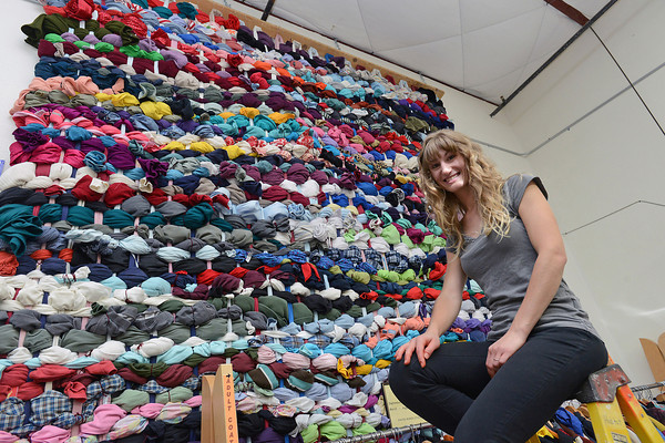 Loveland-based artist Abbie R. Powers poses Tuesday, Sept. 18, 2012 at ReStore in front of an installation piece of a weaving she recently made out of used, but unsalable, clothing.