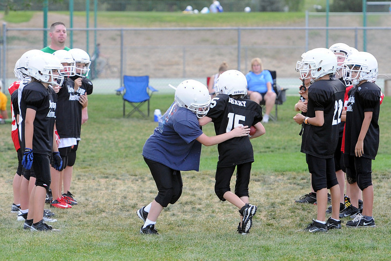 Mikey Berry, 10, middle right, attempts to run past Wyatt Wailes, 10, while working on a drill with teammates on their Advantage Automotive youth football team on Wednesday, Aug. 29, 2012 near Loveland High School.
