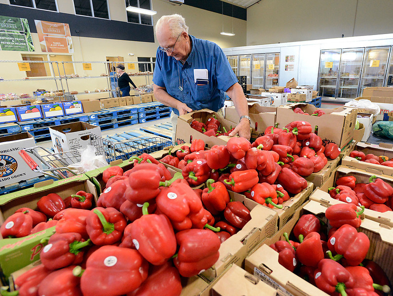 David Kenders of Loveland picks out some red bell peppers Friday at Loveland Food Share. The food share is celebrating its one-year anniversary at this Loveland location.