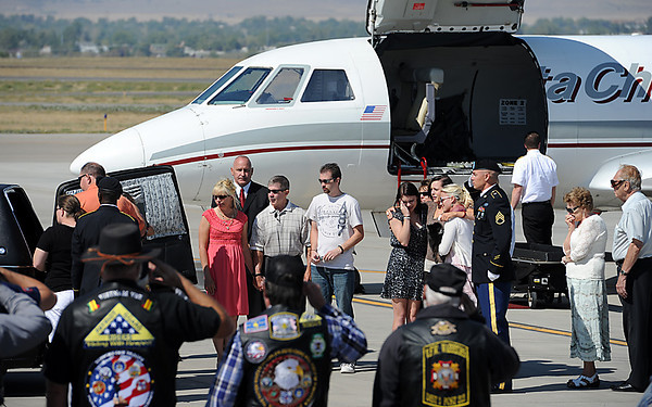 Family and friends of U.S. Army Sgt. Christopher Birdwell comfort each other after his casket is transferred from an airplane to a hearse at the Fort Collins-Loveland Municipal Airport on Wednesday, August 5, 2012. Sgt. Birdwell was killed in action in Afghanistan on August 27, 2012.