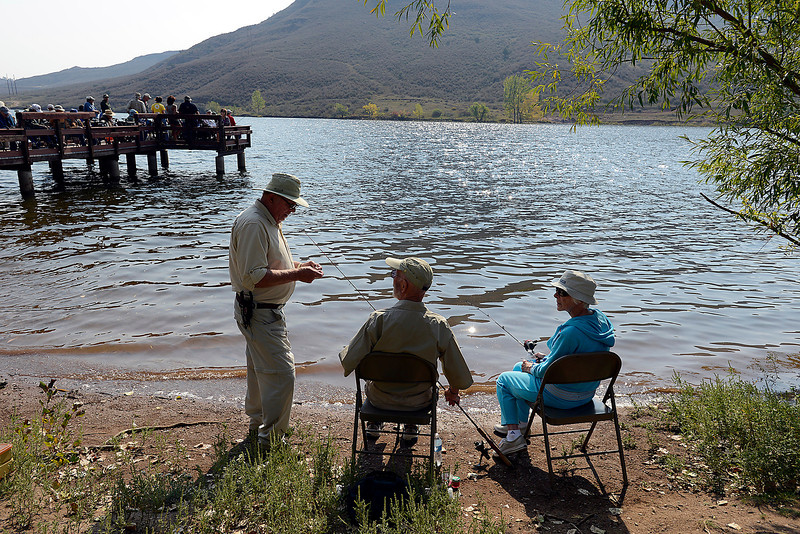 Bob Bulloch, center, gets some help baiting his fishing pole from Loveland Fishing Club member Pat Weller, left, as Dorothy Bulloch, right, hopes for a bite during the Senior Fishing Derby at Flatiron Reservoir on Wednesday.