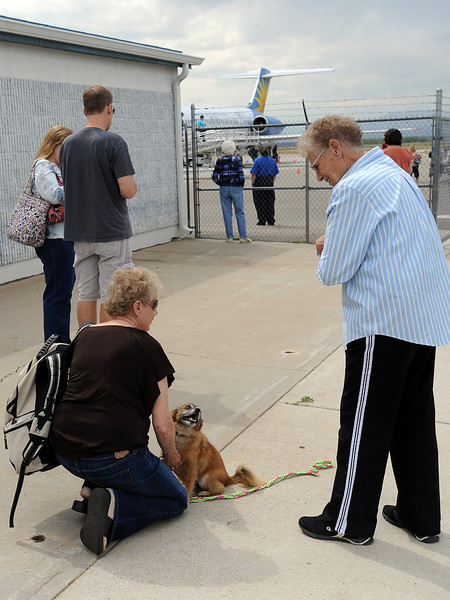 Darlene Fales, right, greets her sister Gloria Brockel, kneeling and petting Fales' dog Dollie, who had just arrived Friday, Sept. 7, 2012 at the Fort Collins/Loveland Municipal Airport on a flight from Las Vegas. The sisters are from Torrington, Wyo. and like the convenience of the airport in Loveland.