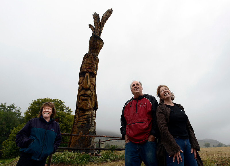 Ranch owner Pat Block, left, Bob Campagna, center, president of NOVO Restoration, and Kristine Rampone, NOVO board member, pose for a photo Wednesday by Redman, a wood sculpture on Block's ranch west of Loveland. NOVO Restoration is raising money to restore the sculpture, which is seen by many motorists from U.S. 34.