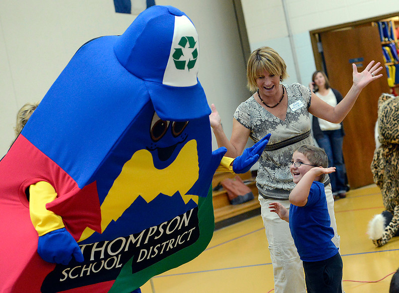 Aaron LaSalle, 5, right, a kindergarten student at Lincoln elementary School, gives a hig-five to the new Thompson School District's recycling mascot as Michelle Malvey, center, encourages him Monday at the school in Loveland. The mascot was unveiled Monday during an assembly to update students on the district's recycling program.