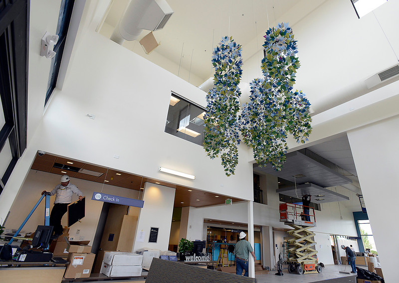 Crews finish work on the new Kaiser Permanente building Thursday in Johnstown in preparation of their Monday opening. A kinetic sculpture by Fort Collins artist Jan Carson hangs in the entrance.