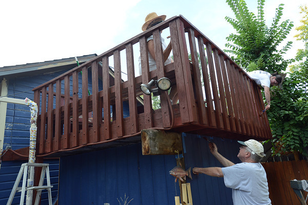 Volunteers Greg Tempel, bottom, Judy McBride, top left, and Emma Pattison, 16, paint a deck Saturday, Sept. 15, 2012 in downtown Loveland during the inaugural Paint Our Town event.