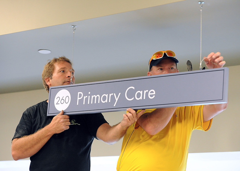 Chad Harr, left, and Joseph Schmidt, with Arapahoe Sign Arts, hang a sign Thursday at the new Kaiser Permanente building in preparation of their Monday opening in Johnstown.
