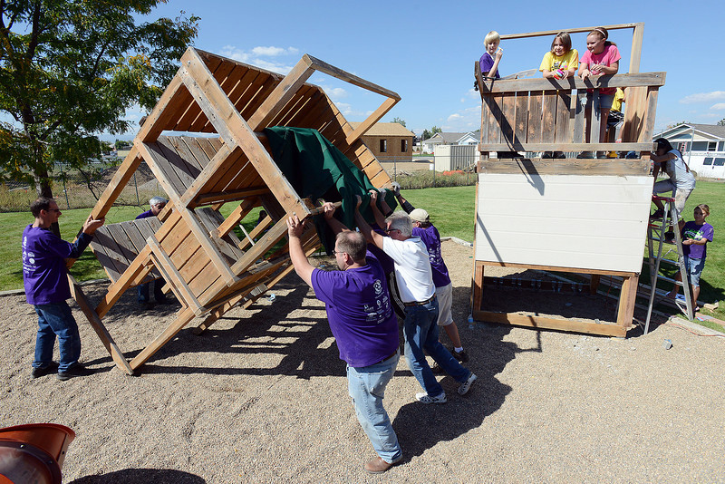 Volunteers and Willow Place residents install playground equipment on Saturday, Sept. 29, 2012 at the housing complex in Loveland during the annual Project One volunteer event.