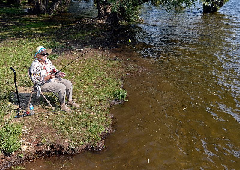 "Iris Thompson of Loveland reels in her line while fishing at Flatiron Reservoir west of Loveland on Wednesday during the second annual Senior Fishing Derby. Thompson said ""This is what I miss more than anything is getting out and fishing. It doesn't matter if you catch anything or not just have fun."""