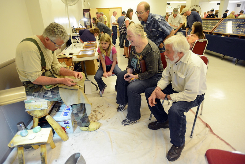 Littleton resident Bill Beekman, left, gives a demonstration on flint knapping technique during the Stoneage Fair on Saturday, Sept. 29, 2012 at the Pulliam Building in downtown Loveland.