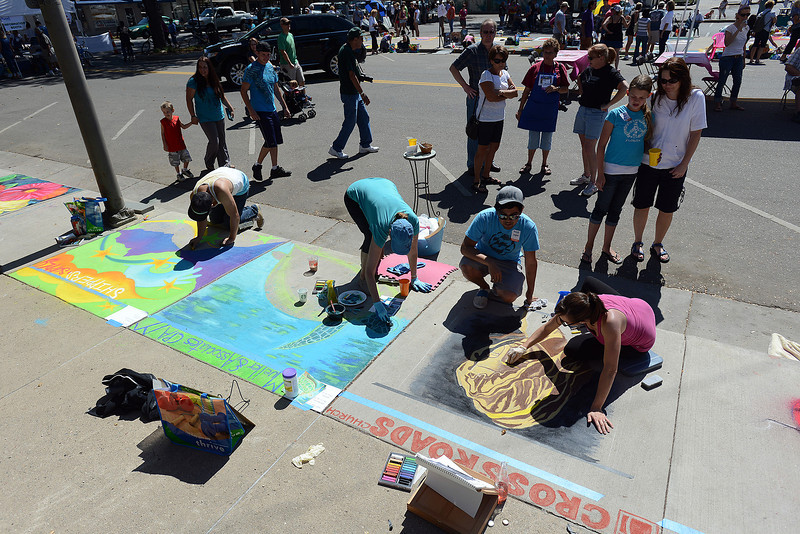 Artists work on chalk drawings on the sidewalk as passers by look on during Pastels on Fifth on Saturday, Sept. 8, 2012 in downtown Loveland.