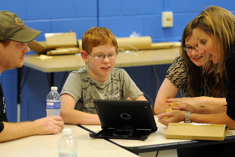 Conrad Ball Middle School sixth-grader Chandler Welch, 11, middle, gets help from teacher Mandy Skinner, right, in setting up the iPad he received on loan from the school while his parents Gale Welch, left, and Jennifer Lakey look on Wednesday, Sept. 19, 2012 at the school.
