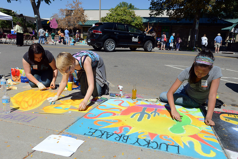 Artists, from left, Cameron Culley, 16, Arrynne Davenport, 16, and Sidney Kress, 13, draw on the sidewalk during Pastels on Fifth on Saturday, Sept. 8, 2012 in downtown Loveland.