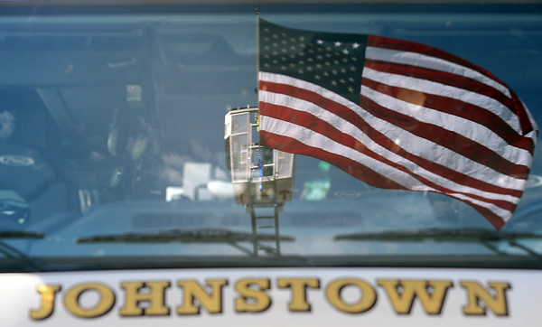 A huge American flag hanging between two ladder trucks from Johnstown and Windsor is reflected in the windshield of a fire truck Friday during Staff Sgt. Christopher Birdwell's memorial service in Loveland.