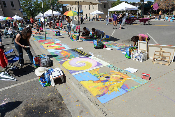 Artists work on chalk drawings that cover the sidewalks during Pastels on Fifth on Saturday, Sept. 8, 2012 in downtown Loveland.