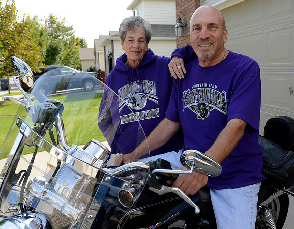 Larry Sanders and his wife Rosalie Sanders pose for a photo by Larry's motorcycle recently at their Loveland home. Sanders, a cancer survivor, said he would sit on his motorcycle to keep his spirits up when he was going through cancer treatments.