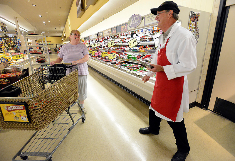 Dan West, jokes with customer Shirley Forrest before getting her a smaller package of stew beef Monday morning at the west Safeway store in Loveland. West has worked for Safeway for 36 years and is retiring on Thursday.