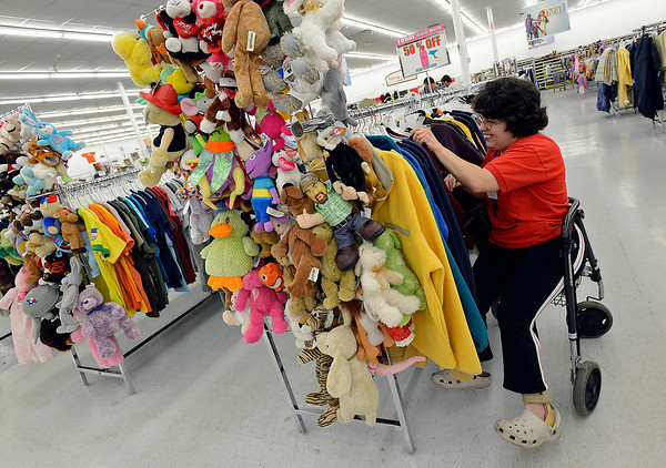 Chandy Jiles, an employee at the ARC Thrift Store in Loveland, straightens merchandise in one of the aisles at the store Friday. Folks can register now to volunteer at this store and many other places for Make A Difference Day, a week long event in October in Loveland.