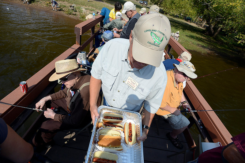 Ray Petersburg, center, a Loveland Fishing Club memeber, delivers hot dogs to folks fishing on the dock Wednesday during the Loveland Fishing Club Senior Fishing Derby at Flatiron Reservoir.
