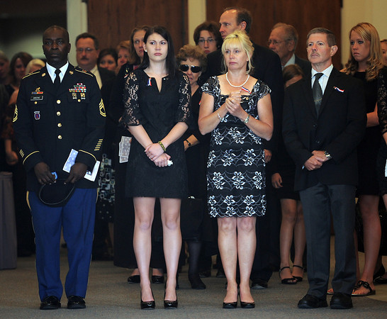 Army Staff Sgt. Christopher Birdwell's family, including his sister Maegan Birdwell, left, his mom Pam Birdwell, center, and his dad Jim Birdwell, right, stand inside the church watching as his casket is loaded into a hearse Friday after his memoiral service in Loveland.