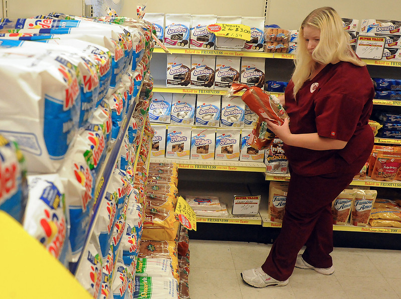 Loveland resident Carrie Vormestrand decides which loaf of bread to buy Thursday at the Wonder Hostes Bakery Outlet in west Loveland. She was shopping with her mother, Nancy, and brother, Aaron. (Photo by Craig Young)