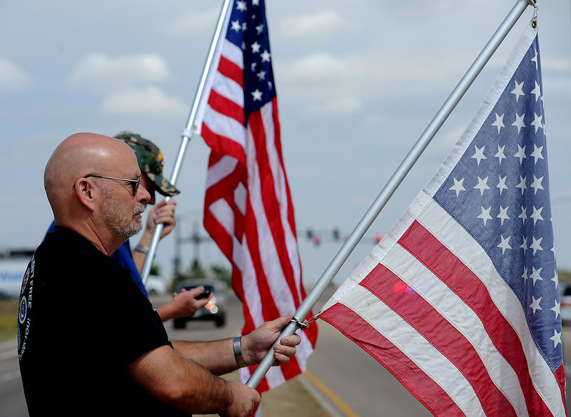 Mark Bolles, front, and Rick Fisher, both of Loveland, hold American flags as the funeral procession for Army Staff Sgt. Christopher Birdwell leaves Resurrection Fellowship Church in Loveland on Firday.
