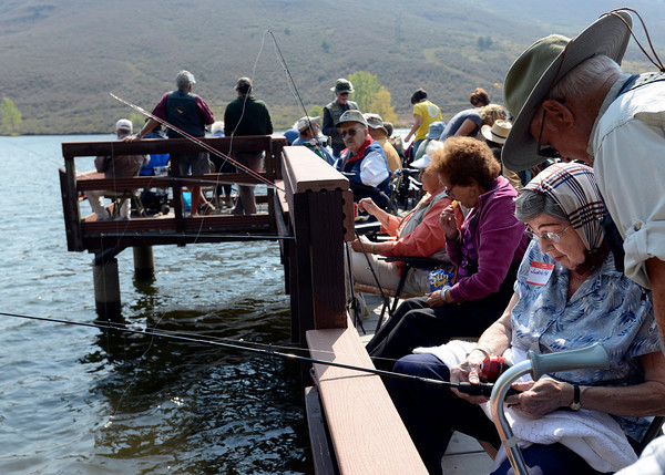 Juanita Adamson of Loveland gets some fishing tips from Jim Giles, right, a Loveland Fishin Club member, Wednesday during the Loveland Fishing Club Senior Fishing Derby at Flatiron Reservoir.