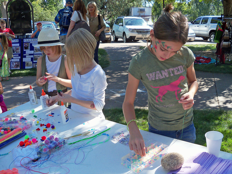 Sarah Seybold, 12, of Longmont, right,Êselects the next bead for her peace necklaceÊat a craft table hosted by the Thompson School District elementary counselors during Peace in the Park on Saturday. Her younger sisters, Shelby Seybold, 9, left, and Skyler Seybold, 8, are making peace pals out of crafting materials.