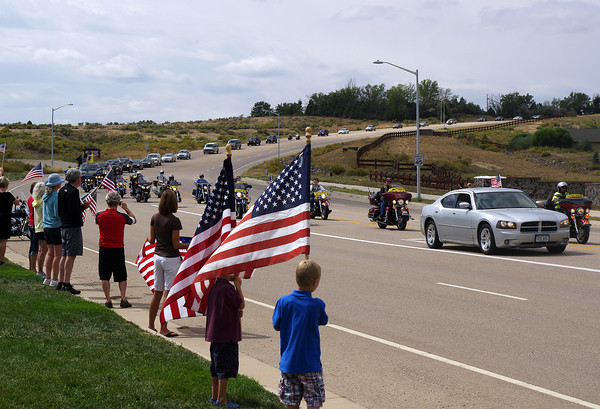 Twin brothers Blake and Brett Barney, 4, wave flags as the funeral procession for Staff Sgt. Christopher Birdwell travels on Crossroads Boulevard Friday following his funeral.