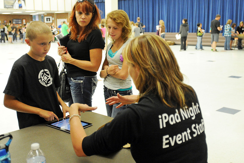 Conrad Ball Middle School sixth-grader Griffin Achziger, 11, left, gets help setting up his iPad tablet computer from teacher Sherri Specht while his mother Laurie Bebbie and sister Avery Achziger, 14, look on during iPad Night on Wednesday, Sept. 19, 2012 at the school.
