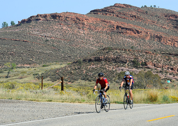 Sean Kellar of Berthoud, left, and Doug Miller of Loveland ride their bikes west on Larimer County Road 18E on their way to Flatiron reservoir during a lunchbreak on Tuesday.