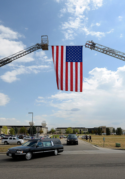 A hearse carrying Staff Sgt. Christopher Birdwell's body travels under a huge American flag hanging by two ladder trucks as the procession leaves the church Friday.