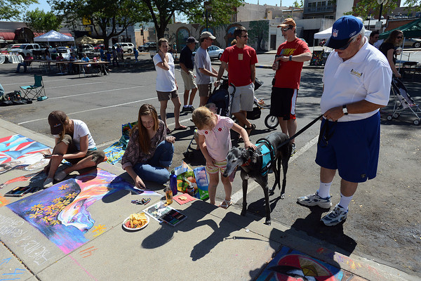 Tom Carrigan, right, his greyhound dog named Lucca and 6-year-old Madisen Bounds look on as artists Hannah Circenis and Jaime Gastelle participate in Pastels on Fifth on Saturday, Sept. 8, 2012 in downtown Loveland.