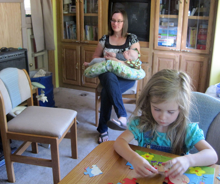 Alexa Brewer (foreground) puts together a puzzle while her mother, Kayleigh, talks about the decision to move into a recreational vehicle for several years. Kayleigh and her husband, Sevren, have started a blog to recount the adventures they'll have.
