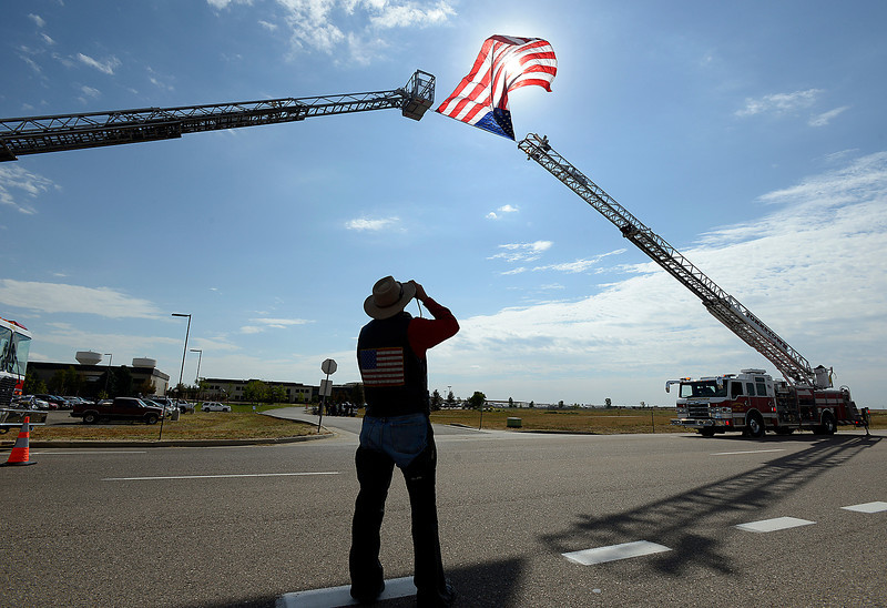Patroit Guard Rider Jay Hill takes a photo of an American flag waving in the wind between two ladder trucks Friday during Staff Sgt. Christopher Birdwell's memorial service.