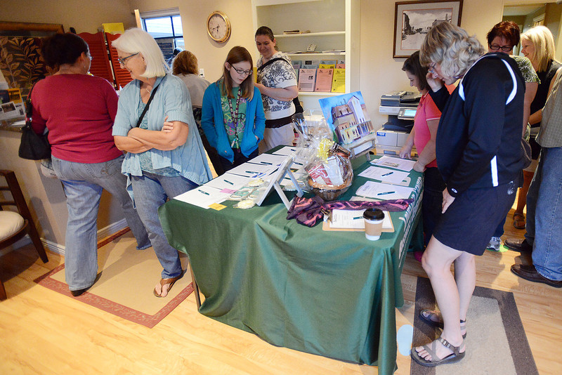 Michelle Myers, front right, and others look at items available to bid on during a silent auction Friday, Sept. 14, 2012 at the Loveland Center for Business Development during the Night on the Town event.