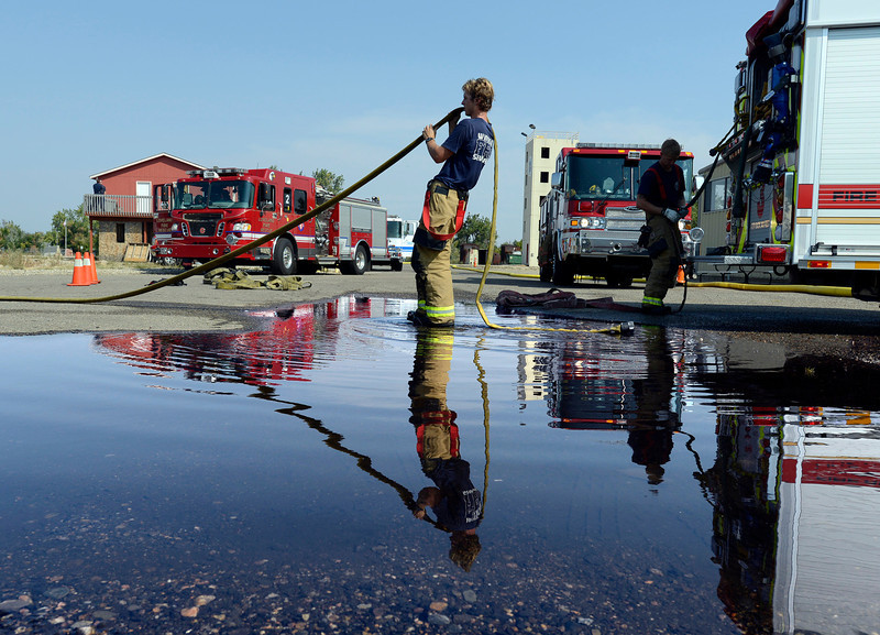 Firefighters from Loveland Fire and Rescue, Poudre Fire Authority and Windsor Severence Fire Protection District pack up equipment during a training exercise in Loveland on Thursday. Bryan Vogt, center, a Windsor firefighter, removes water from a fire hose after the rural area simulation where crews used an extended hose lay like they would in many rural fire situations.