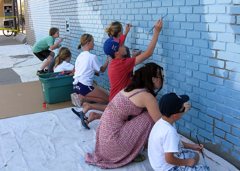 Artist Stephanie Ruelas and her son, 8-year-old Adam Ruelas, work on a mural on the Aims Community College building Sunday along with local students.
